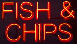 Fish and chips restaurant neon sign at night in street photo.