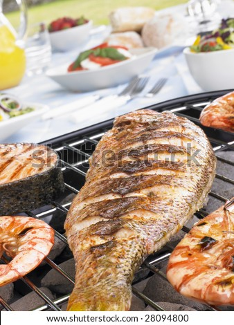Fish And Prawns Cooking On A Grill - stock photo