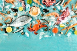 Fish and seafood background with a place for text, a flat lay overhead shot. Sea bream. shrimps, crab, sardines, squid, mussels, octopus and scallops