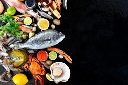 Fish and seafood background with copy space, a flat lay top shot. Sea bream, crab, squid, scallops on black with a place for text