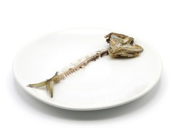 Fish bones of mackerel in white plate on white background in food scraps of millionaires are the food for the poor, wasteful and greedily concept.