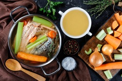 fish broth or soup of salmon, onion, carrot, celery, herbs and spices in a stockpot and in a white bowl on a concrete table with ingredients, free space, horizontal view from above, flat lay, close-up