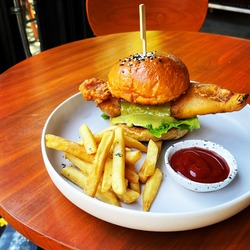 Fish burger fries,frenchfries and tomato sause.On wood table.
