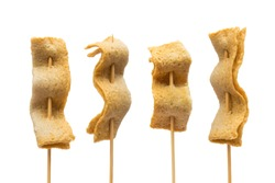 Fish cake on the wooden skewer on white background.