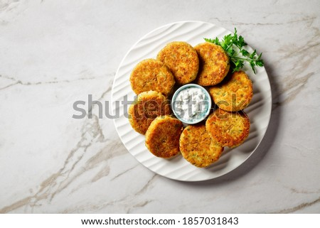 Fish cakes of cod or haddock fillet with potato and parsley, breaded in breadcrumbs on a white plate with tartar sauce in a gravy boat on a light marble stone background,  top view, close-up ストックフォト ©