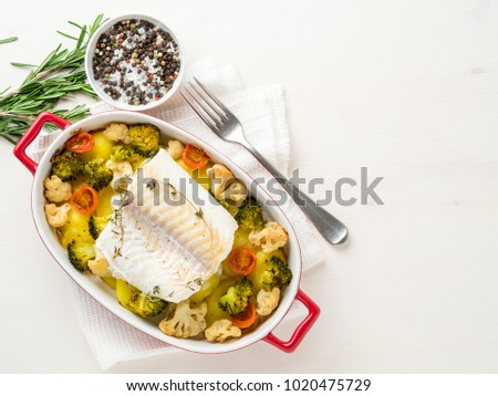 Fish cod baked in the oven with vegetables - healthy diet healthy food. Light white wooden  background, copy space, top view.