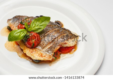 fish: cod or perch baked with vegetables on a white background