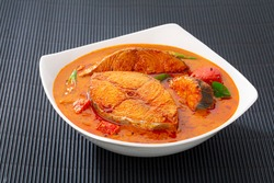 Fish curry_Seer fish curry ,traditional Indian fish curry ,kerala special dish using coconut ,arranged in a white bowl garnished with curry leaves  on black textured  background, isolated.