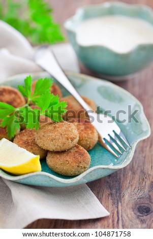 Fish cutlets and yogurt sauce, selective focus