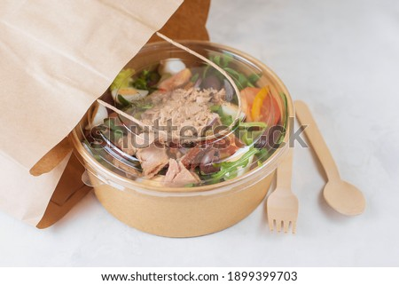 Fish diet salad with tuna, tomatoes, arugula on light background. Healthy vegetarian lunch. Concept eco restaurant delivery, environment protection. Take away food in brown paper craft plate.