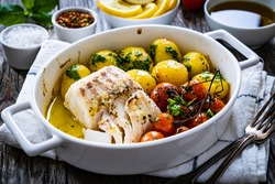 Fish dish - baked cod fillet with potatoes and cherry tomatoes on wooden table