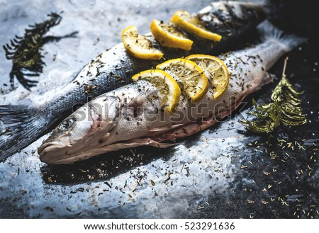 Fish dish cooking with various ingredients. Raw Sea bass with lemon, garlic, herbs and spices on cutting board, top view. Healthy food or diet nutrition concept.  #523291636