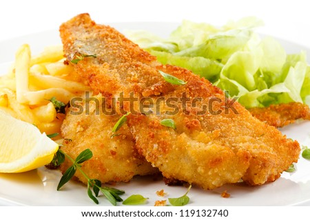 Fish dish - fried fish fillet with vegetables on white background