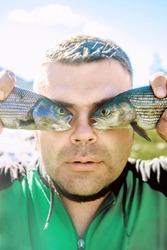 fish eye. outdoor photo of a young handsome man holding two fishes before eyes.