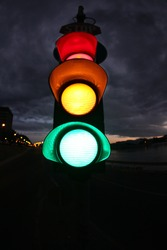 Fish eye photo from a traffic lamp. Photo was taken  at night. All lamps (red, yellow, green) are lighting.