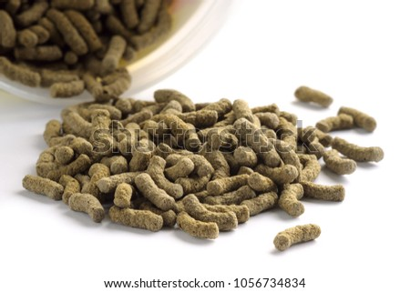 Fish feed isolated on white background. Fish food in sticks for large aquarium and pond fish #1056734834