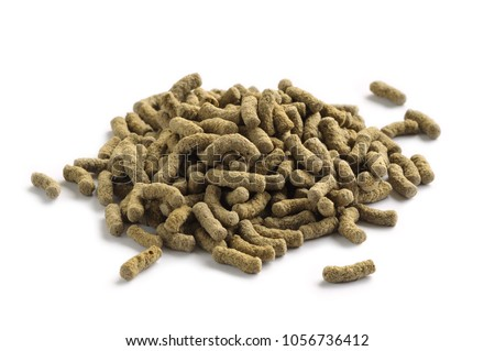 Fish feed isolated on white background. Fish food in sticks for large aquarium and pond fish #1056736412