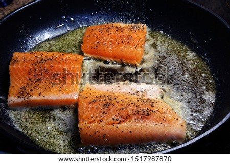 Fish fillet steaks frying on a skillet. Roasting orange salmon or trout fillets with pan. Delicious seafood cooking. Сток-фото ©