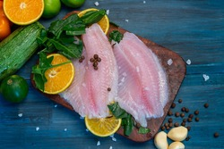 Fish fillet with orange, grain salt, pepper and spinach, on a blue wooden base, ready to cook
