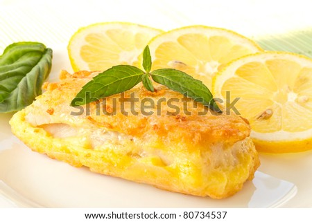 Fish  Batter on Fish Fillets Fried In Batter With Lemon And Basil On A Plate