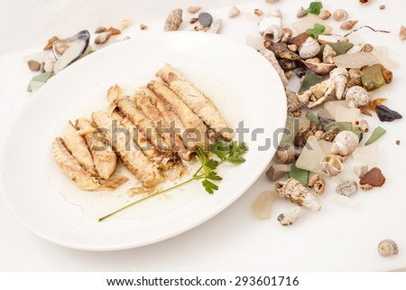 Fish fillets roasted mackerel on a white plate with parsley and shells.