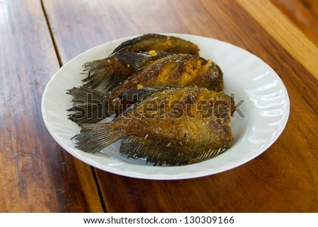 Fish fried in white dish on wooden table