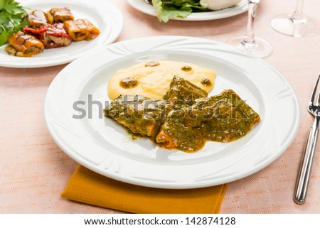 Fish in savory sauce with polenta