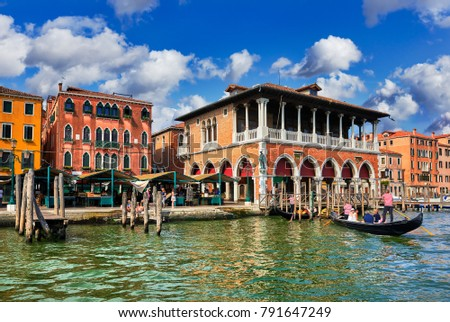 Fish market on Grand Canal in Venice Italy vintage building famous landmark picturesque landscape summery day with blue sky and white clouds.