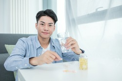 fish oil capsules and a glass of water in the hands of a man