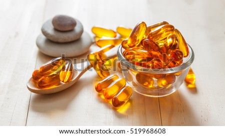 Fish oil capsules on wooden background and texture, vitamin D supplement, selective focus