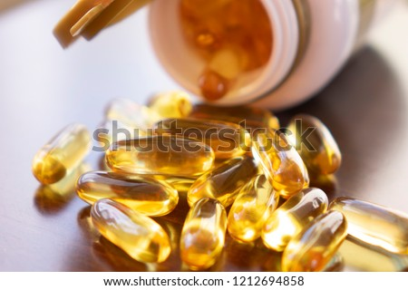 Fish oil capsules with omega 3 and vitamin D in a glass bottle on wooden texture, healthy diet concept,close up shot.