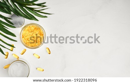 Fish oil capsules with omega 3 and vitamin D in a glass jar on a white concrete table top view, healthy eating concept. Cod liver oil softgels, layout with copy space Сток-фото ©
