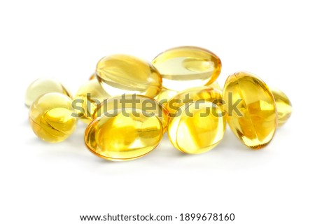 Fish oil gel capsules isolated on white background. Pile of yellow fish oil capsules isolated on white background. Omega-3 fish oil capsules. Close-up of yellow fish oil capsules.