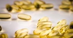 Fish Oil Omega 3 golden capsules on black blackground
