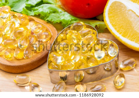 Fish oil, soft capsule, omega 3, supplement food vitamin D capsules in Heart shaped  with vegetables and fruit greens tomato lemon on wood . still life of healthy food and supplementary  diet concept #1186928092