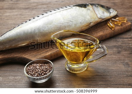 Fish oil with flax grain and fish on wooden background