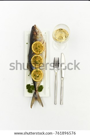 Fish on a plate with lemon, a glass of water fork knife. #761896576