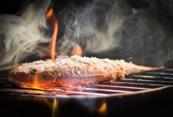 Fish on grill / Close up of seafood grilled fish food with salt on the grill fire and smoke on dark background