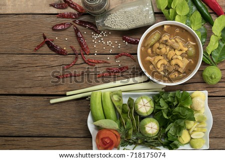Fish organs sour soup with cashew nuts in white bowl and vegetables for ingredient soup on wooden table.Still life style for thai food and Selective focus. Imagine de stoc ©