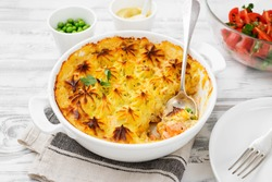 Fish pie with salmon, mashed potatoes, green peas and creamy sauce. on white wooden background