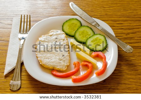 Fish salad on bread with cucumber and pepper on a plate