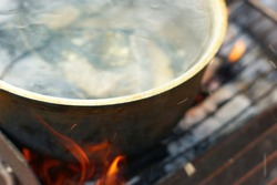 Fish soup - uha - with grayling cooked in large castiron pot at bonfire
