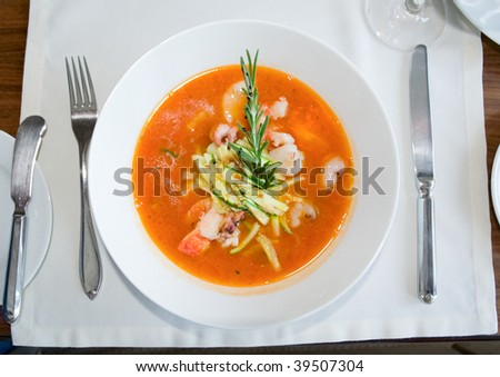 Fish soup with rosemary on restaurant table