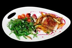 Fish steak with vegetable ratatoille and rocket salad, isolated on black