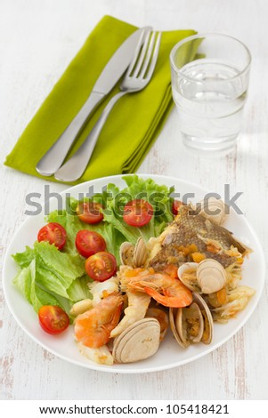 fish stew with salad on the white plate
