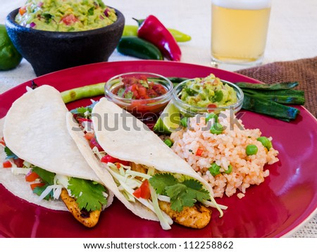 Fish Tacos with Guacamole and Rice: Seasoned grilled fish tacos in corn tortillas with salsa, cabbage, guacamole, lime, rice, and beer.