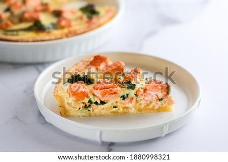 Fish tart. Tart. Piece of pie. Kish lauren slice. Quiche lauren with red fish cut off piece. Quiche with salmon, spinach and broccoli. Writing dough pie. Fish pie. Salmon