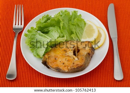 fish with salad and lemon on the white plate