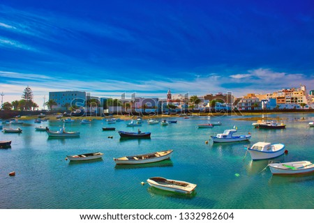 Fisher boats at the laguna Charco de San Gines and the tower of the historic church Iglesia de San Gines at sunshine, city of Arrecife, Lanzarote, Canary Islands Foto stock ©