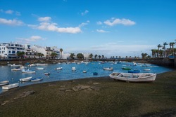 Fisher boats at the laguna Charco de San Gines at sunset, city of Arrecife, Lanzarote, Canary Islands. October 2019